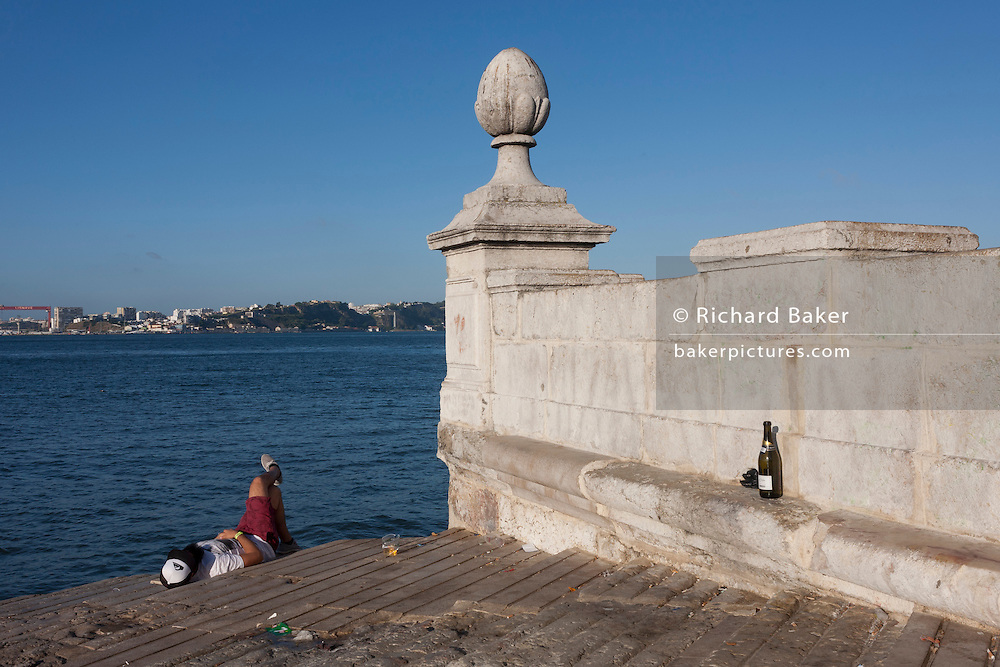 A sleeping man next to a bottle on the riverfront beach of Lisbon's Praca do Commercio.
