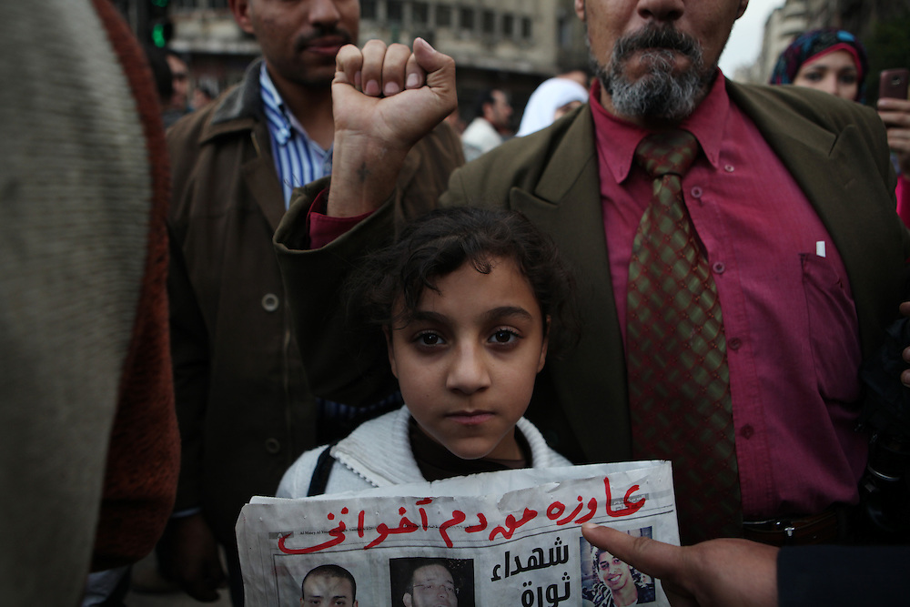 "On ""Sunday of the martyrs"" at Tahrir Square, an Egyptian girl holds a newspaper with pictures of some of the more than 300 pro-democracy protesters killed in clashes with government forces. Her father behind her holds up a tattoo on his wrist to show that it's not only Muslims active in the protests."