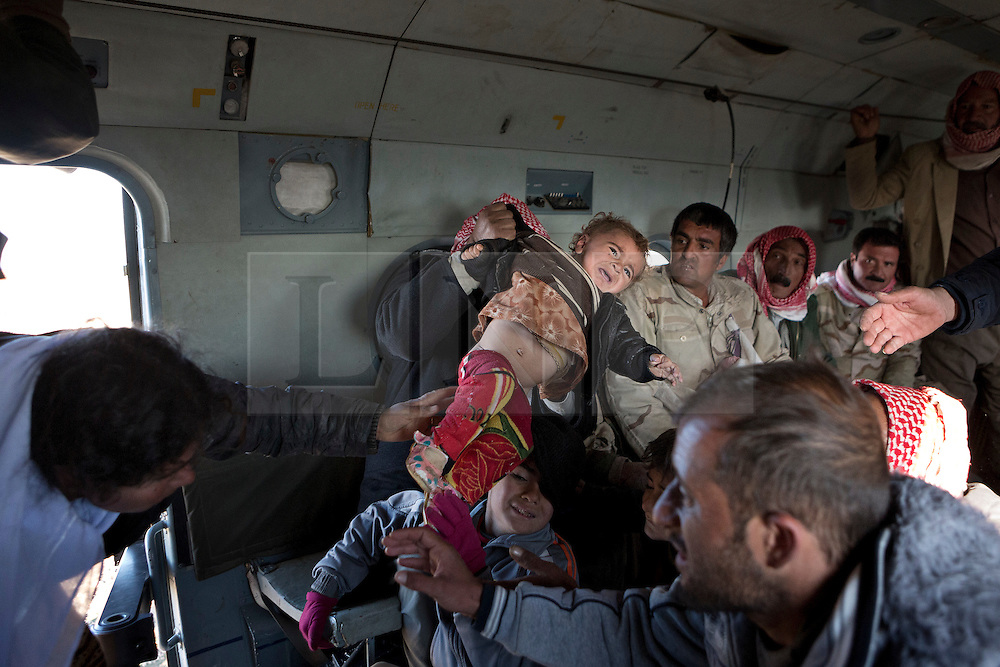 &copy; Licensed to London News Pictures. 11/12/2014. Sinjar Mountains, Iraq. A young Yazidi refugee is handed through the door of Iraqi Air Force Mi-17 Hip helicopter by his or her mother as they are evacuated from Mount Sinjar.<br /> <br /> Although a well publicised exodus of Yazidi refugees took place from Mount Sinjar in August 2014 many still remain on top of the 75 km long ridge-line, with estimates varying from 2000-8000 people, after a corridor kept open by Syrian-Kurdish YPG fighters collapsed during an Islamic State offensive. The mountain is now surrounded on all sides with winter closing in, the only chance of escape or supply being by Iraqi Air Force helicopters. Photo credit: Matt Cetti-Roberts/LNP