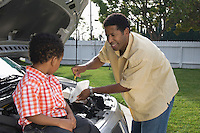 Boy (5-6) assisting father checking oil level in car
