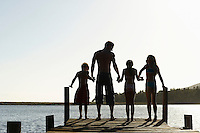 Three children (7-9) holding hands with father standing on edge of dock back view.