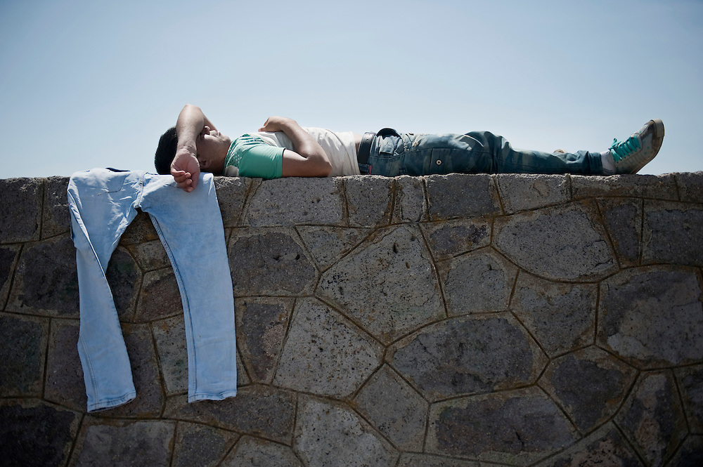An Afghan man rests on the seawall of Molyvos port hours after his boat has been rescued by the Greek Coast Guard. Everyday hundreds of refugees, mainly from Syria and Afghanistan, are crossing in small overcrowded inflatable boats the 6 mile channel from the Turkish coast to the island of Lesbos in Greece.