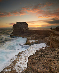 A romantic couple enjoy the sunset together beside the Pulpit Rock whilst ocean waves break over the rock ledges behind them.<br /> <br /> Portland Bill in Dorset, England