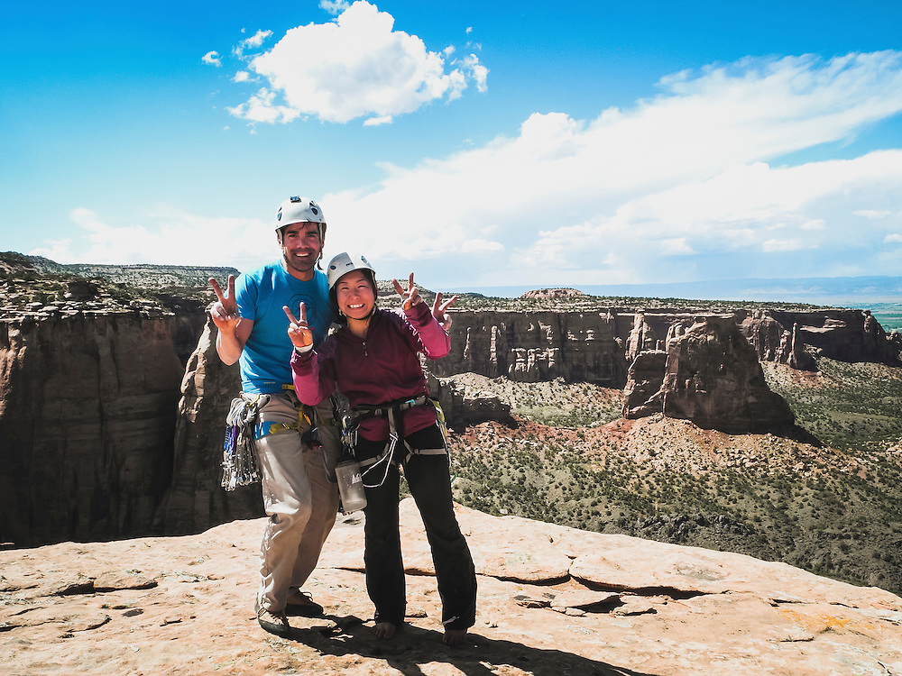 Louis Arevalo and Shiho Kobayashi strike the classic Japanese pose from the summit of Kissing Couple Spire (Bell Tower), Colorado National Monument.