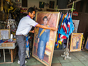 10 AUGUST 2016 - BANGKOK, THAILAND: A man buys a portrait of Queen Sirikit to display on her birthday. Thais are preparing for the Queen's birthday. Queen Sirikit of Thailand, was born Mom Rajawongse Sirikit Kitiyakara on 12 August 1932. She married  Bhumibol Adulyadej, King of Thailand (Rama IX) in 1950. He is the longest serving monarch in the world and she is longest serving consort of a monarch. Her birthday, like the King's Birthday (which falls on Dec. 5),  is a national holiday in Thailand. Her birthday, August 12, is also celebrated as Mothers' Day in Thailand. Thais hang portraits of Queen Sirikit in their homes and fly her royal flag on her birthday.        PHOTO BY JACK KURTZ