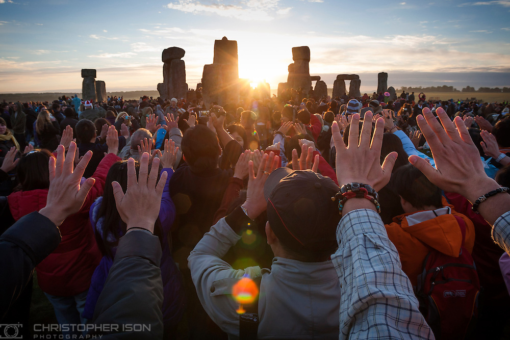 Visitors the the World Heritage site at Stonehenge in Wiltshire watch the sunrise during the summer solstice.