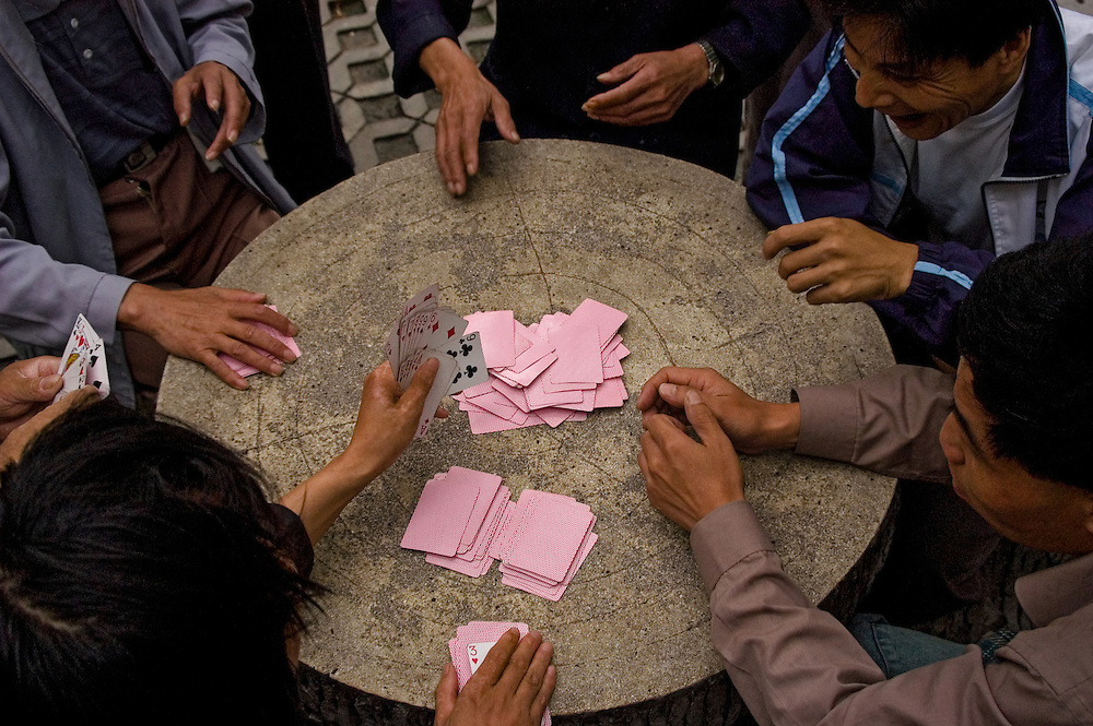 Close-up of an intense game of cards in a Shanghai park.
