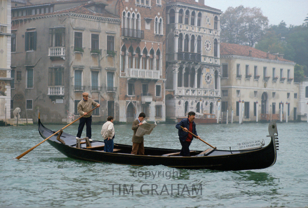 On a grey day in Venice a man commuting by gondola on the canal stands up to read his newspaper.