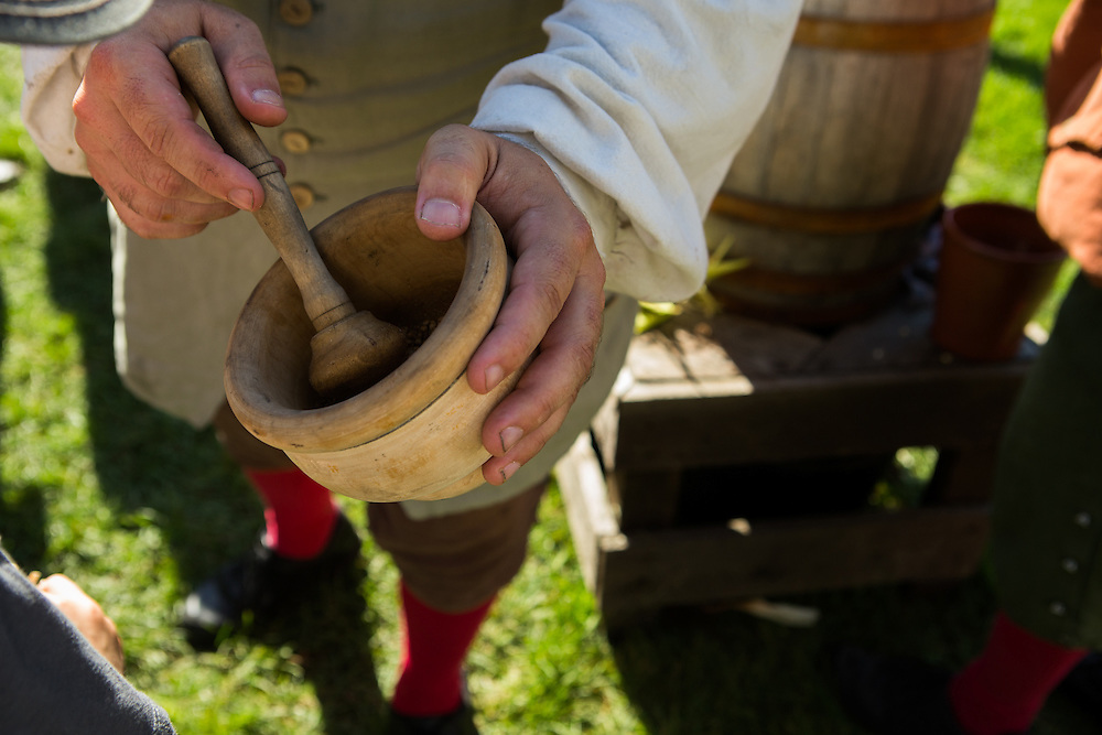 A presenter is grinding spices with a mortar and pestle as part of the mead making process during Fall Flavors at Greenfield Village.