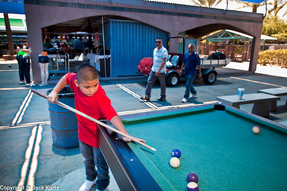 July 25 - PHOENIX, AZ: ANGEL GUTIERREZ, 12, plays pool in El Gran Mercado. El Gran Mercado (The Big Market) in Phoenix is the largest flea market in the Phoenix area and has served the area's immigrant community for more than 20 years. With more than 150 small independent stalls selling Mexican clothes, cowboy hats, Mariachi music and food stalls selling Mexican favorites like birria chivo (goat stew) and menudo (tripe) it was more like a Mexican market than an American mall. Business in the mercado is down more than half this year because many immigrant families, legal and illegal, are leaving Arizona before the state's tough new anti-immigrant law, SB 1070 goes into effect on July 29. SB 1070 allows local police officers to check the immigration status of people they have probable cause to believe may be in the US illegally and requires immigrants to carry their immigration papers with them at all times.    Photo by Jack Kurtz