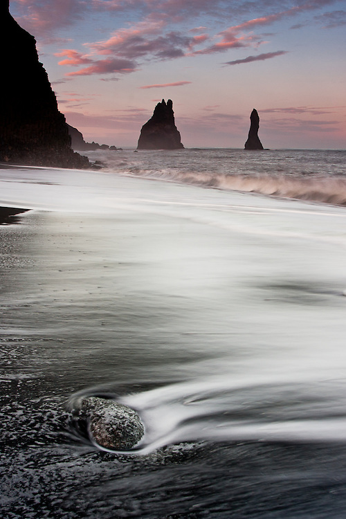 At Reynisfjara Beach, the white surf of the breaking waves contrasts with the black volcanic sand and rocks.