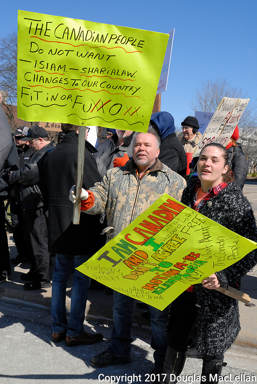 CANADA, Windsor. 04 March 2017. A Canadian Coalition of Concerned Citizens demonstration at City Hall at noon is met by a counter demonstration group. There is some minor pushing, heated debate and occasional threats. The demonstration is spurred in part by M-103, a federal anti-Islamophobia motion. NOTE: Agefotostock exclusive license, G99-2864919, to license go to http://www.agefotostock.com/age/en/Stock-Images/Rights-Managed/G99-2864919