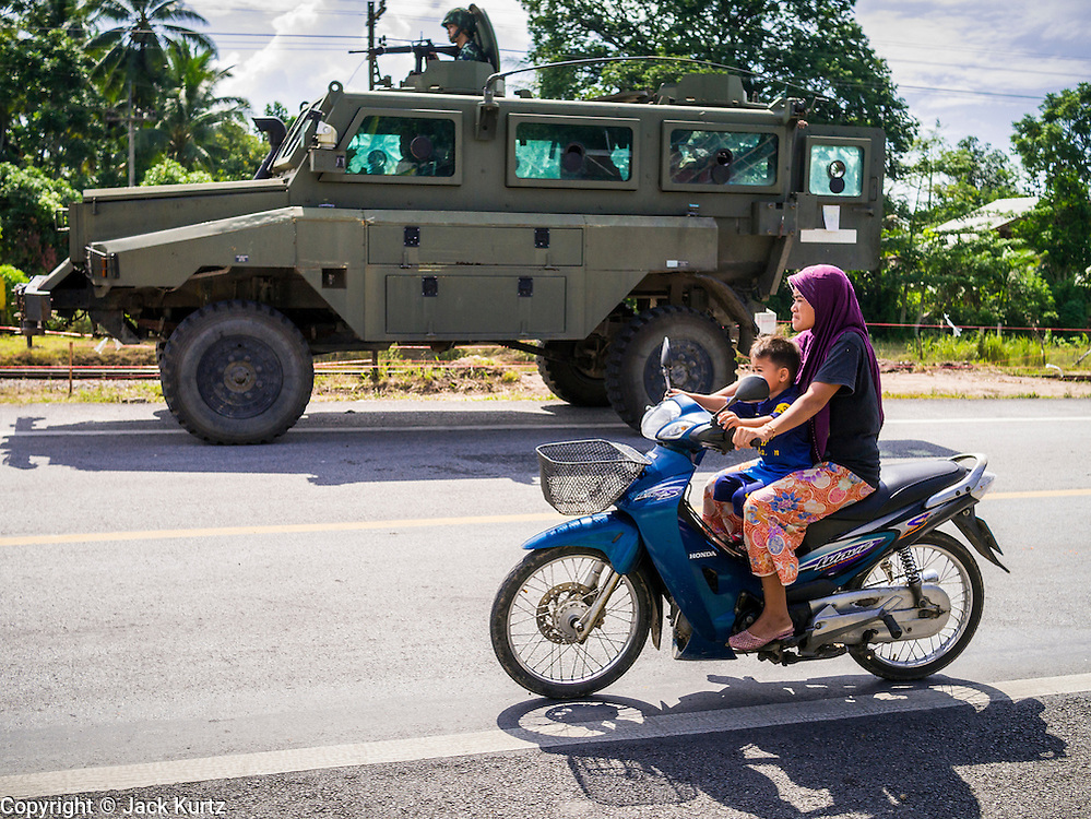 11 JULY 2013 - RAMAN, YALA, THAILAND: A Muslim woman and her son ride their motorcycle past a Thai army REVA 4x4 MKII Armoured Personnel Carrier guarding the scene of an IED attack against a Thai Army unit. Eight soldiers were injured when the IED exploded under a Thai Army truck carrying soldiers back to their camp after they finished a teacher protection mision. The army routinely dispatches soldiers to protect teachers and Buddhist monks, who have been targeted by Muslim insurgents as representatives of the Bangkok government. More than 5,000 people have been killed and over 9,000 hurt in more than 11,000 incidents in Thailand's three southernmost provinces and four districts of Songkhla since the insurgent violence erupted in January 2004, according to Deep South Watch, an independent research organization that monitors violence in Thailand's deep south region that borders Malaysia.    PHOTO BY JACK KURTZ