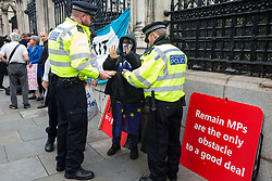 "London, UK. 25 September, 2019. Metropolitan Police officers detain a masked protester outside the Houses of Parliament on the day after the Supreme Court ruled that the Prime Minister's decision to suspend parliament was ""unlawful, void and of no effect""."