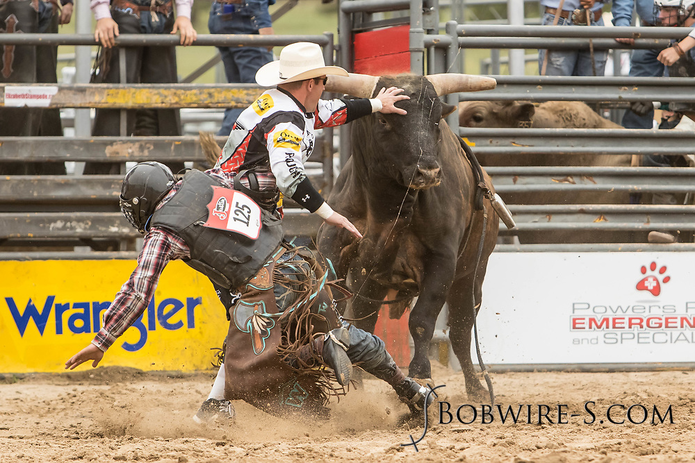 Bullfighters Nate Jestes (light shirt) and Cade Burns come to the aid of bull rider Logan Hunter after his ride on Summit Pro Rodeo's All Better during the third performance of the Elizabeth Stampede on Sunday, June 3, 2018.
