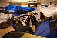 """Un manifestant dans la partie Sud du camp qui regroupe des dizaines de tentes et quelques abris de fortune. // Le mouvement spontane du """"15 M"""" (15 mai) compose de citoyens espagnols campe depuis 2 semaines sur la place Puerta Del Sol avec pour revendication la construction d'une democratie nouvelle. Organise en commission les citoyens prennent la parole lors d'assemblee ouverte a tous - Place Puerta Del Sol à Madrid le Juin 2011. ©Benjamin Girette/IP3Press"""