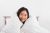 Portrait of happy woman wrapped in quilt on bed