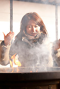 A young Japanese lady putting incense smoke on her head to receive blessings from the Osu Kanon temple deity.