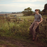 Landscape portrait of young man sitting on a stone wall in a field