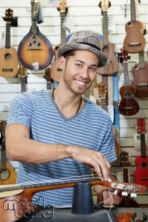 Portrait of a happy owner of music store restringing guitar