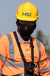 West Hyde, UK. 14th September, 2020. A HS2 security guard watches environmental activists from HS2 Rebellion who blocked a gate to the South Portal site for the HS2 high-speed rail link. Anti-HS2 activists blocked two gates to the same works site for the controversial £106bn rail link, one remaining closed for over six hours and another for over twelve hours.