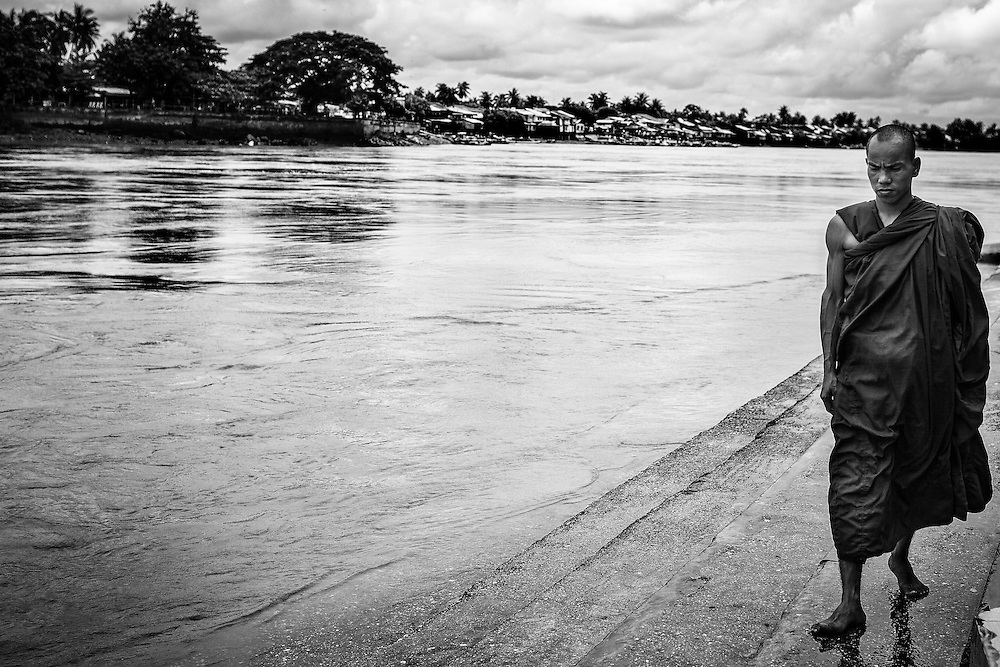 A monk walks near the water's edge at Ya Le Pagoda, which rests on an island in the middle of the river, year Yangon, Myanmar.