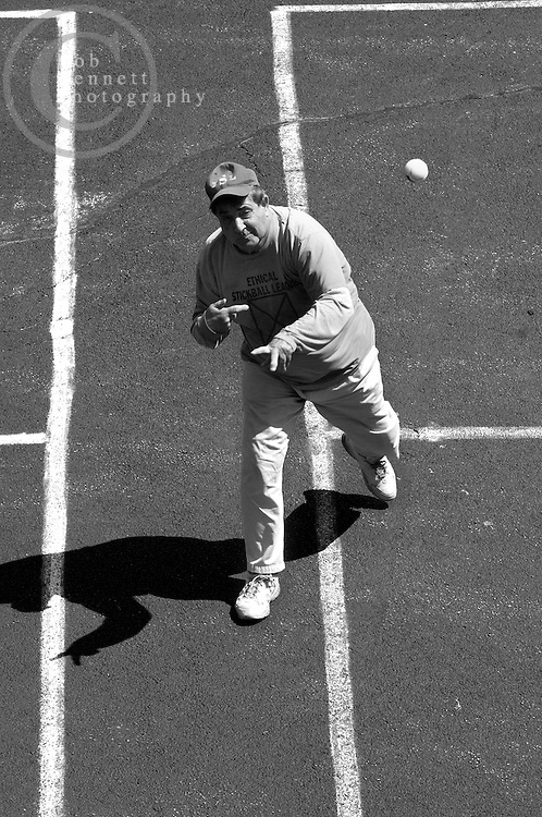 """Howard """"Hit Man"""" Weishaus, 68 and a teacher from New City, pitches during a game of stickball as seen from a second story school window..---.The Ethical Stickball League has been operating since 1970, meeting every Sunday in the parking lot behind Hastings High School from 10:30AM to 1PM.  The players are men now mostly in their 70s - carrying nicknames like """"The Wise One"""", """"Hit Man"""" and """"Plays Hurt"""" - who have an affiliation with the school, either as former teachers, students or neighbors. As their slogan suggests, all it takes for a few hours of """"Aestas Aeterna"""" (Eternal Summer) is an outside temperature above 45 degrees and 8 willing souls...CREDIT: Rob Bennett for The NY Times"""