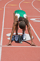 Female athlete in starting block ready to run