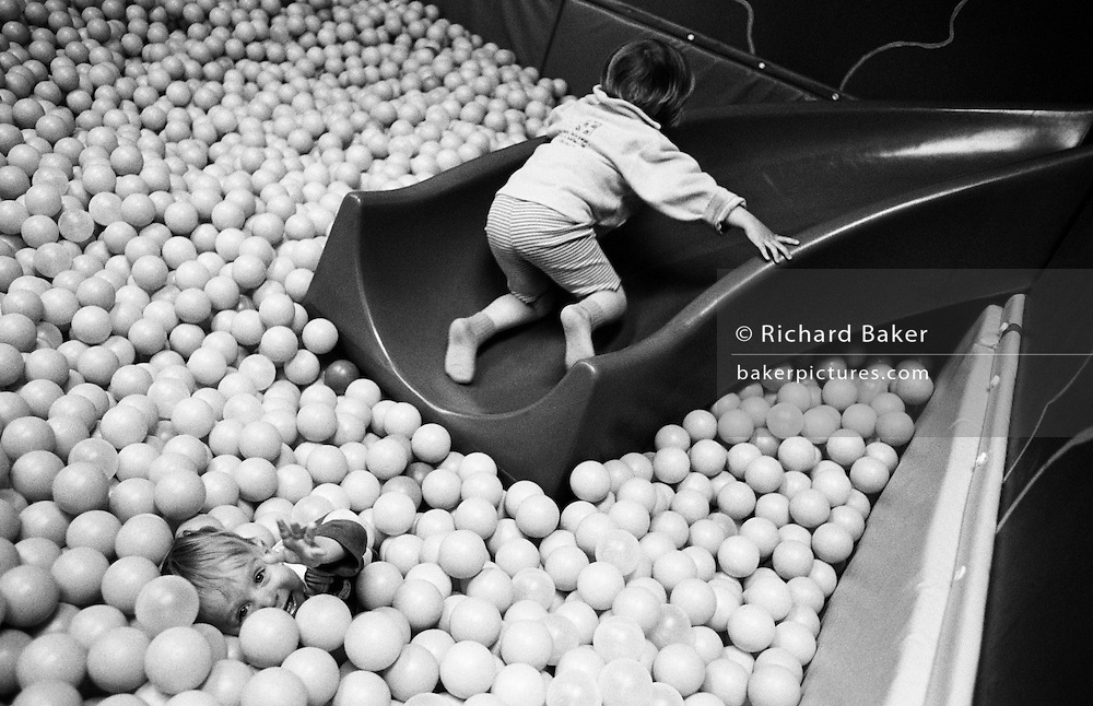 "While her brother apparently sinks beneath the surface of plastic balls, a three year-old girl scrabbles up a small slide in the Croydon branch of IKEAS's crèche facility, allowing parent shoppers to browse the store while their children frolic in the ball pond. Designed to encourage adventure and stimulate developing senses, the kids play on their own in this safe environment. From a personal documentary project entitled ""Next of Kin"" about the photographer's two children's early years spent in parallel universes. Model released."
