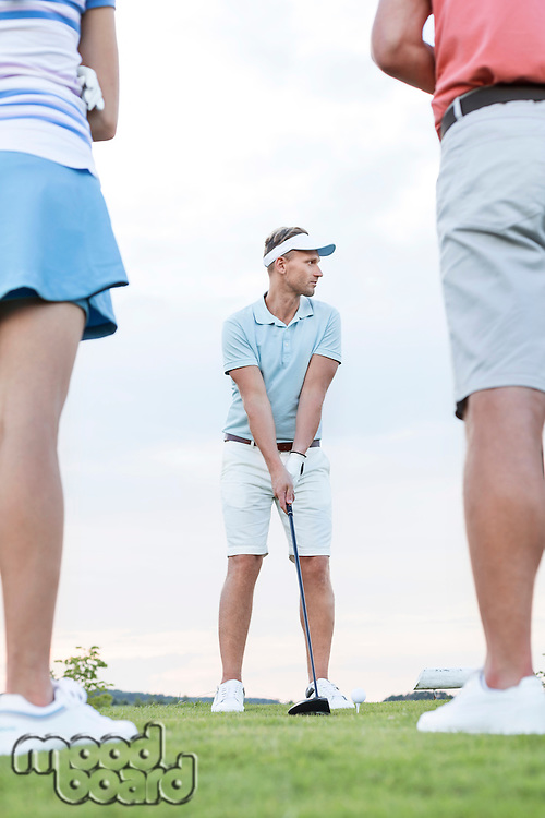Man playing golf against sky with friends standing in foreground