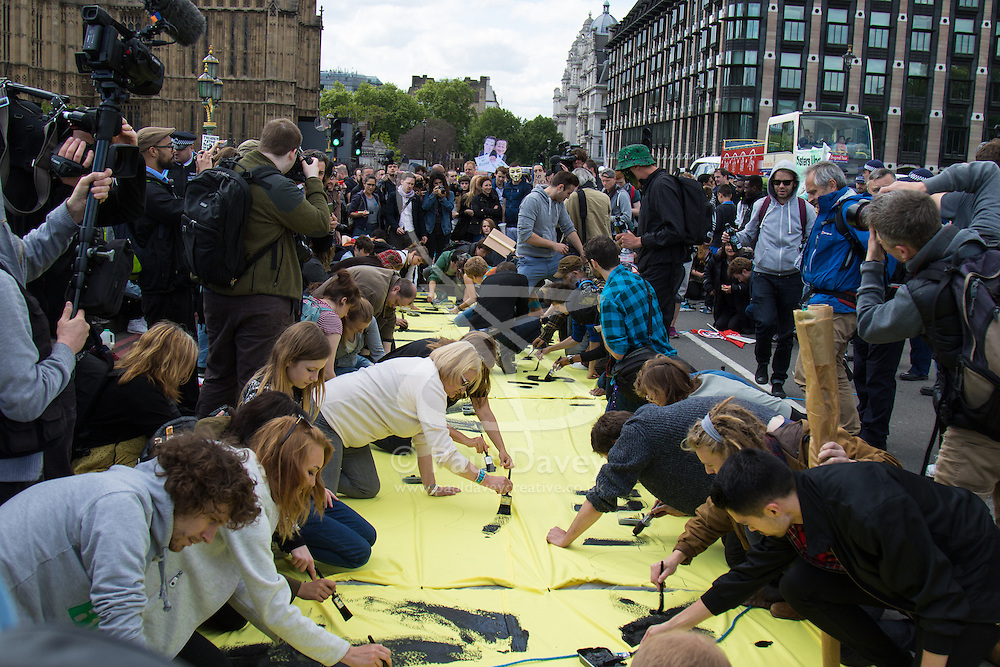 ter, London, May 30th 2015. Anti-austerity campaigners bring traffic on Westminster Bridge as they paint and hang a banner off the bridge highlighting an alleged £120 billion owed in taxes as compared to the proposed £12 billion cuts to welfare. PICTURED: Protesters paint their banner on the road surface of Westminster Bridge.