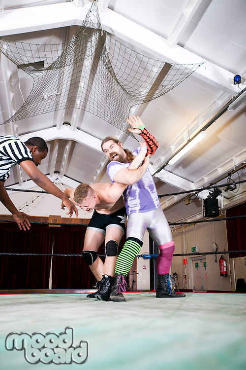 Aggressive wrestler fighting with rival in ring
