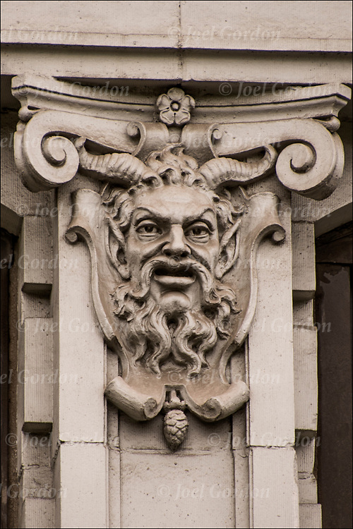 Stonework of Devil's face on side of 19th century building of carved face  in the East Village, NYC