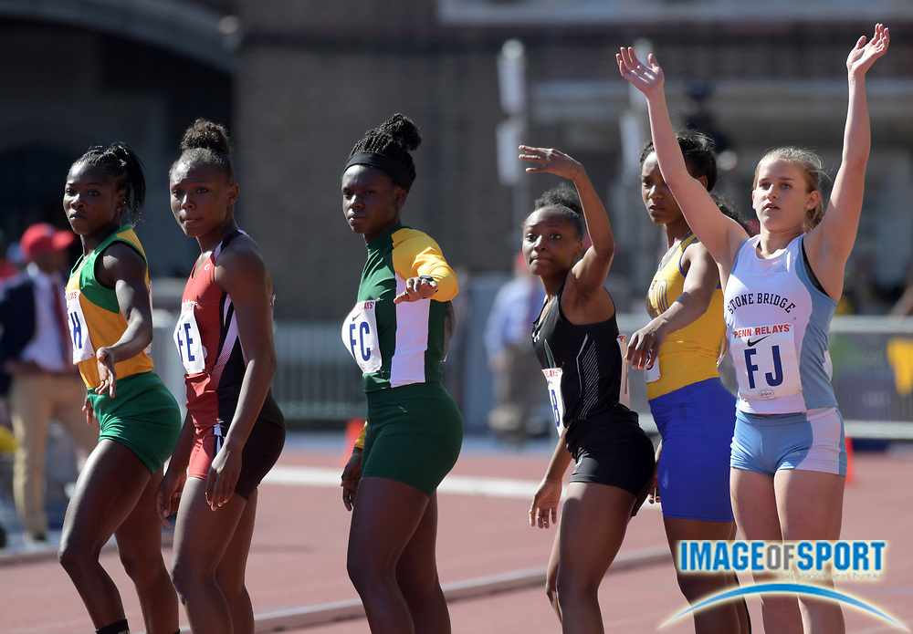 Apr 26, 2018; Philadelphia, PA, USA; Runners await the handoff in a girls 4 x 400m relay heat during the 124th Penn Relays at Franklin Field.