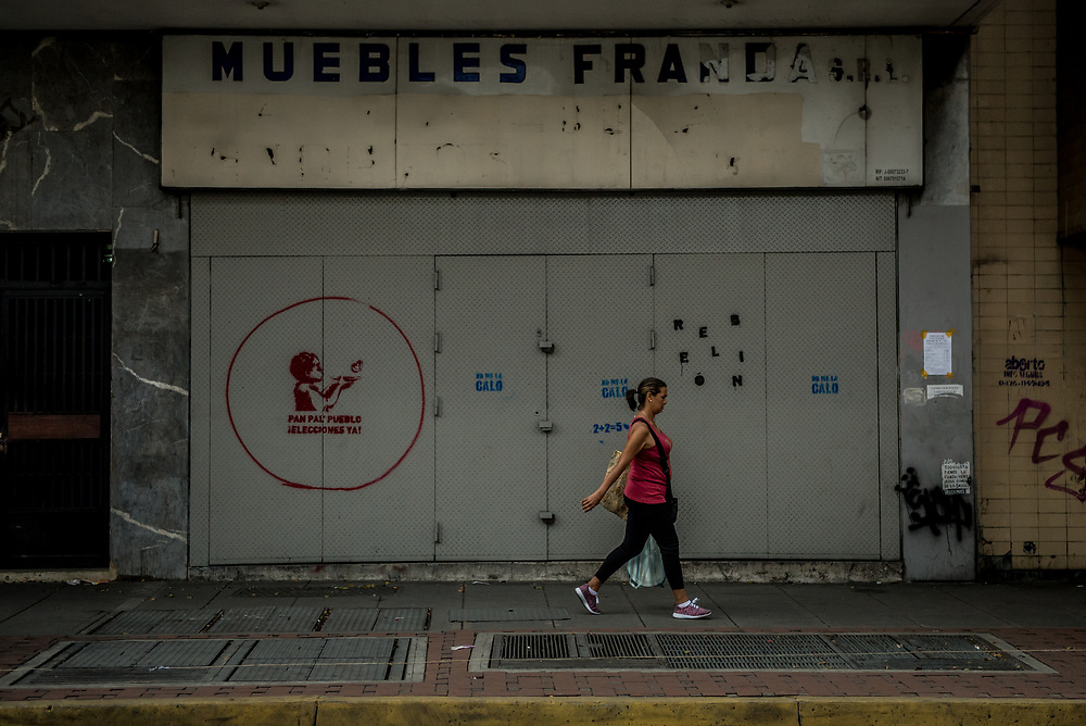 CARACAS, VENEZUELA - JULY 27, 2017: A woman walks past a shop closed in support of a national strike. The political opposition called for a 48 hour national strike for July 26th and 27th, and for their supporters to close businesses, not go to work, and instead create barricades to block off their streets.  Opposition controlled areas of the country were completely shut down.  The strike was called as part of the opposition's civil resistance movement - that began on April 1st, to protest against the Socialist government's attempt to elect a new constituent assembly that will have the power to re-write the constitution, and will threaten democracy.  PHOTO: Meridith Kohut for The New York Times