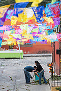 Mexican families spread marigold flowers along the road decorated with papel picado banners in preparation for a Dead of the Dead procession during the Dia de Muertos festival in San Miguel de Allende, Mexico. The multi-day festival is to remember friends and family members who have died using calaveras, aztec marigolds, alfeniques, papel picado and the favorite foods and beverages of the departed.