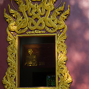 An ornate temple window. Open with golden image of the King of Thailand lit by a ray of sunshine inside. Wat Chedi Ngam in Fang, Chiang Rai, Thailand.