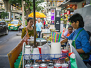 "30 MARCH 2013 - BANGKOK, THAILAND: A coffee vendor makes a drink for a customer on an upscale stretch of Sukhumvit Road in Bangkok. Thailand's economic expansion since the 1970 has dramatically reduced both the amount of poverty and the severity of poverty in Thailand. At the same time, the gap between the very rich in Thailand and the very poor has grown so that income disparity is greater now than it was in 1970. Thailand scores .42 on the ""Ginni Index"" which measures income disparity on a scale of 0 (perfect income equality) to 1 (absolute inequality in which one person owns everything). Sweden has the best Ginni score (.23), Thailand's score is slightly better than the US score of .45.  PHOTO BY JACK KURTZ"