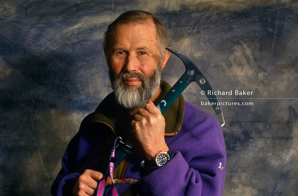 Portrait of the renowned British mountaineer,  adventurer, lecturer and writer Sir Chris Bonnington photographed at his home called Badger Hill, in Wigton, Cumbria, England. Bonnington is seen wearing a fleece against a backdrop holding an ice-axe used on a previous Himalayan mountain expedition. Bonnigton is best known for his 1975 expedition to conquer Mount Everest though he was formerly an army officer in the Royal Tank Regiment before making mountaineering and the writing of these sometimes tragic outcomes a career.