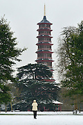 © Licensed to London News Pictures. 19/01/2013. Kew, UK A woman photographs the garden's famous  Chinese Pagoda. People enjoy the snow at Kew Gardens in West London today 19th January 2013. More cold weather and snow are expected over the coming days.  Photo credit : Stephen Simpson/LNP