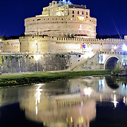 ROME, Italy - The historic round jail, the Castel Sant'Angelo, is reflected on the still waters of the Tiber river at night in Rome, Italy.