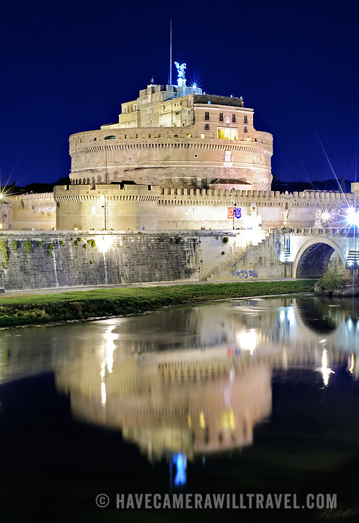 The historic round jail, the Castel Sant'Angelo, is reflected on the still waters of the Tiber river at night in Rome, Italy.