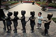 On Shamian Island in Guangzhou, a child near a sculpture representing school children.