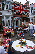 A giant Union jack hangs from an Edwardian house as neighbours hold a street party in honour of Queen Elizabeth's Golden Jubilee celebrations, on 3rd June 2002, in Herne Hill, south London, England.