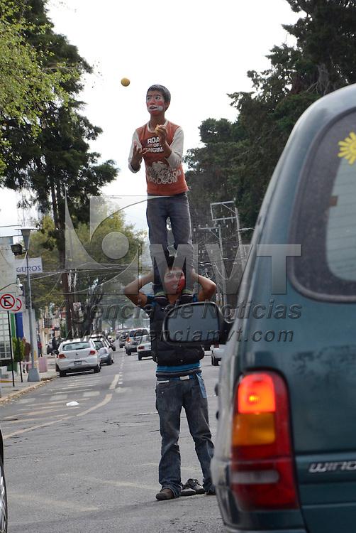 Toluca, Méx.- Dos jóvenes realizan malabares en la avenida Morelos para obtener algunas monedas de los automovilistas que pasan por el lugar. Agencia MVT / José Hernández
