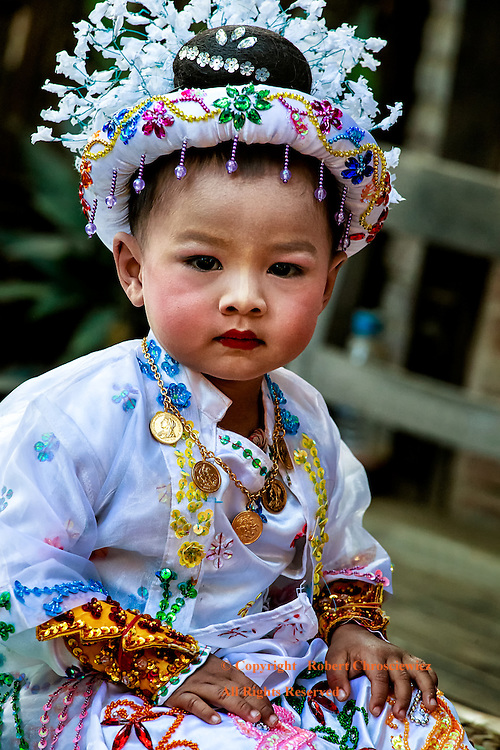 Childs' Initiation: A very young girl is dressed in a fine traditional dress and head dress, ready for the Buddhist initiation of Shinbyu, where this rite of passage allows for a girl to either, be able to wear ear rings, or, to become a Buddhist Nun, Myinkaba Myanmar.