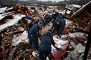 Japanese forces remove a dead body from rubble in the town of Taro after the earthquake and tsunami hit the city on 11 March 2011.