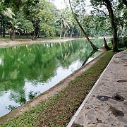 A walkway along the shore of a small lake at the Hanoi Botanical Gardens (Vuon Bach Thao).