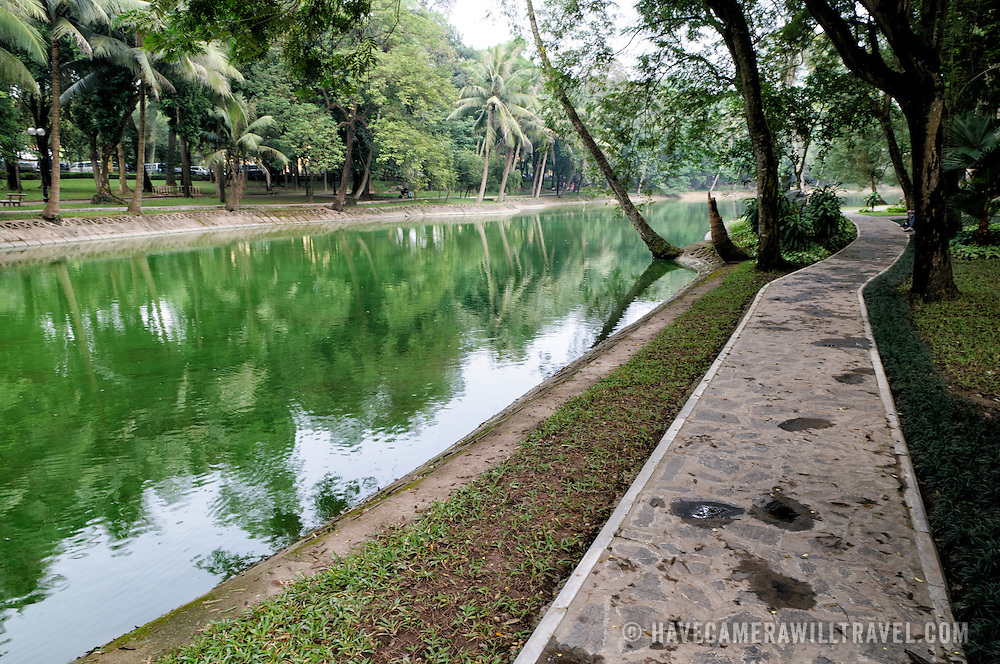 A walkway along the shore of a small lake at the Hanoi Botanical Gardens (Vuon Bach Thao).