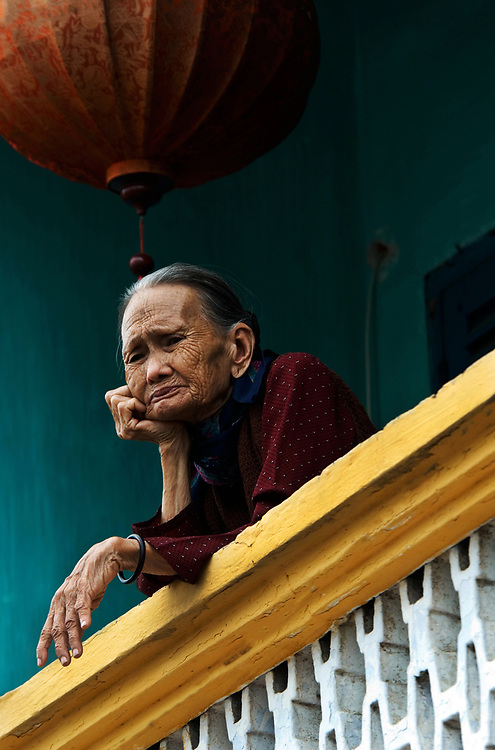 An elderly local lady surveys the street from her balcony. Originally colonised by Chinese merchants, this traditional Vietnamese fishing community of Hoi An largely escaped damage during both the American and French Wars.Now protected by UNESCO, much of the original architecture remains in tact, providing a timeless reminder of the traditions of Vietnam.